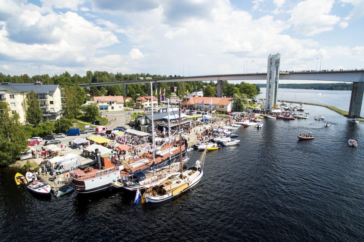 Aurinkoisena kesäpäivänä satamatori on paljon myyjiä ja ihmisiä ja satamalaiturissa on kymmeniä laivoja ja veneitä.
